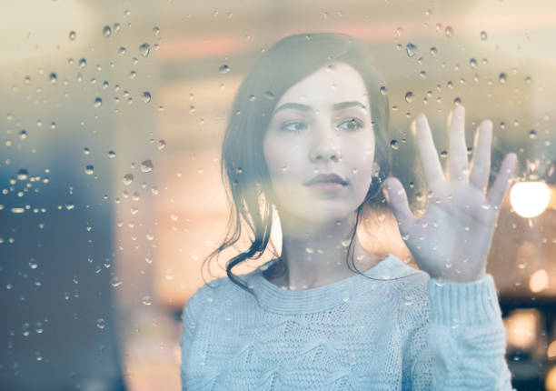 Sad young cute woman looking through window on rainy day stock photo