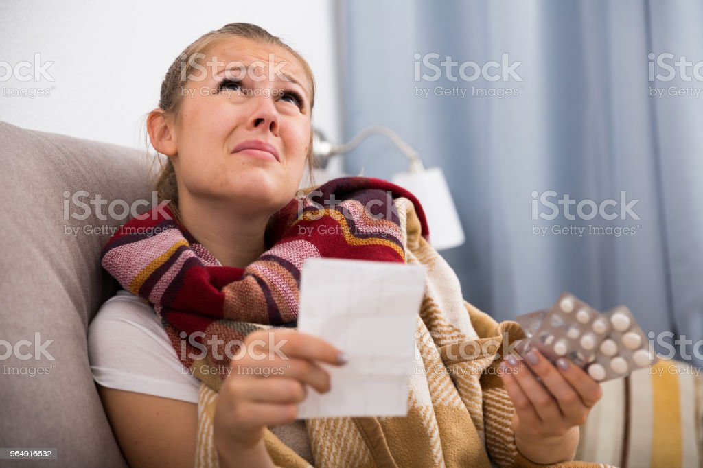 Sad young female reading recipe with pills royalty-free stock photo