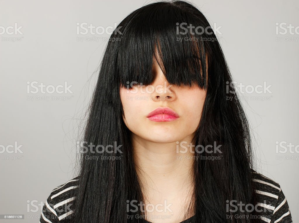 Sad young girl hides her face with bangs stock photo