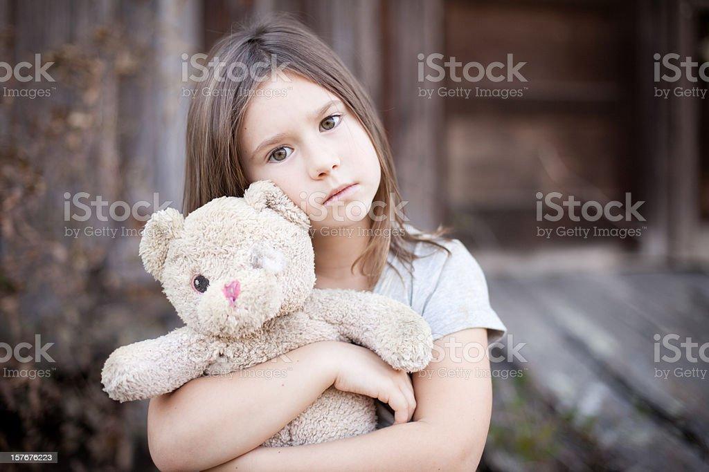 Sad Young Girl Hugging Old, Raggedy Teddy Bear royalty-free stock photo