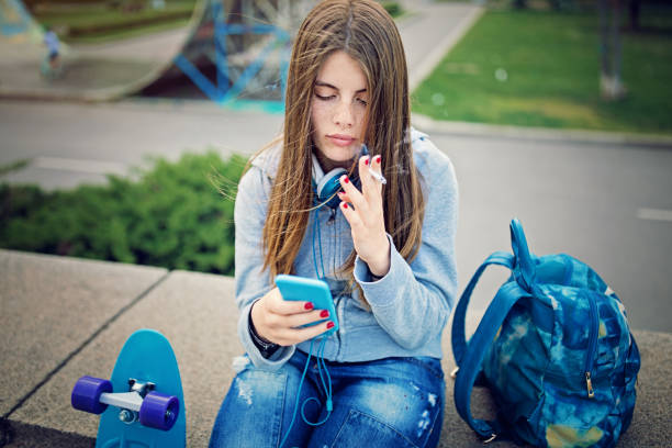 Sad young girl is smoking at the front of skateboard ramp stock photo