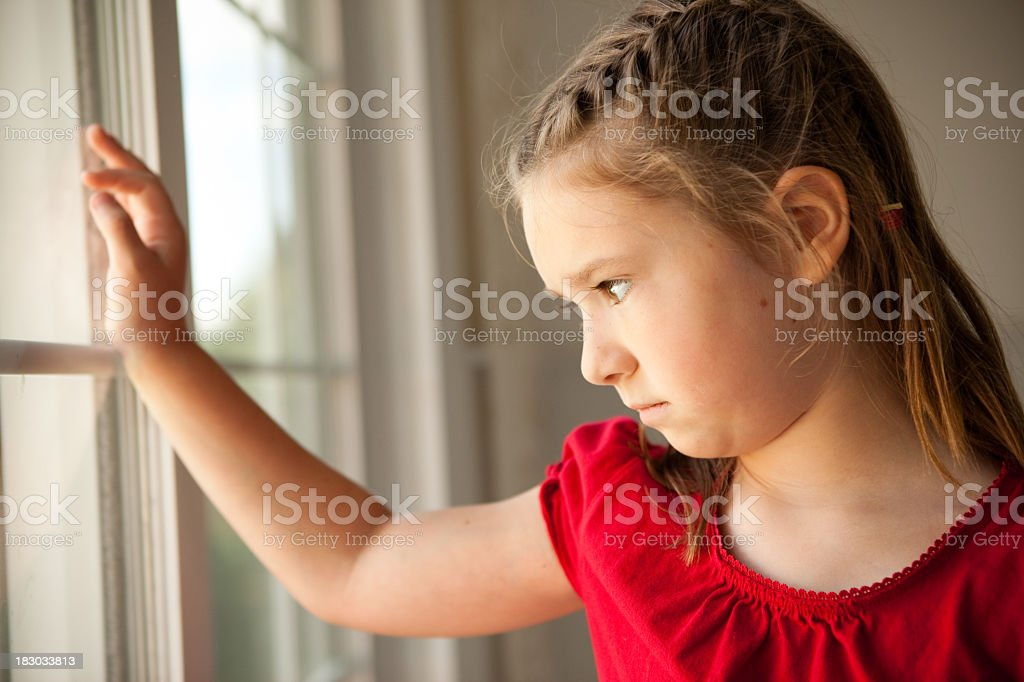 Sad Young Girl Looking Out of Window royalty-free stock photo