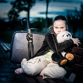 Sad young girl sitting on a bench and hugging her panda
