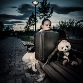 Sad young girl sitting on a bench and touching her panda toy