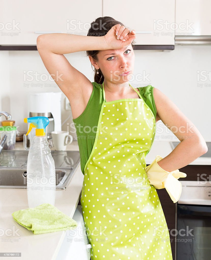 Sad young housewife cleaning furniture stock photo