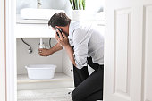 Sad Young Man Calling Plumber In Front Of Water Leaking From Sink Pipe