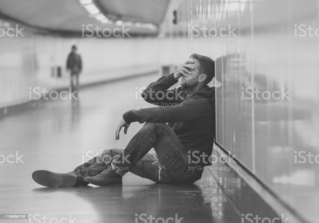 Sad young man crying suffering depression stress sitting on ground...