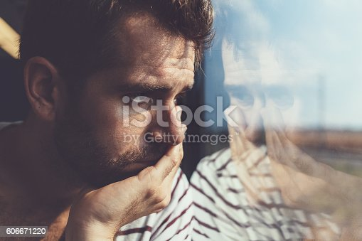 istock Sad young man looking through the window 606671220