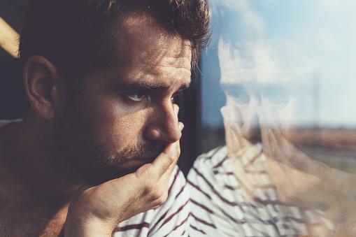istock Sad young man looking through the window 606671220