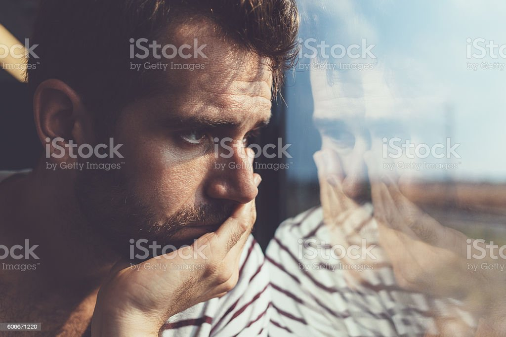 Sad young man looking through the window stock photo