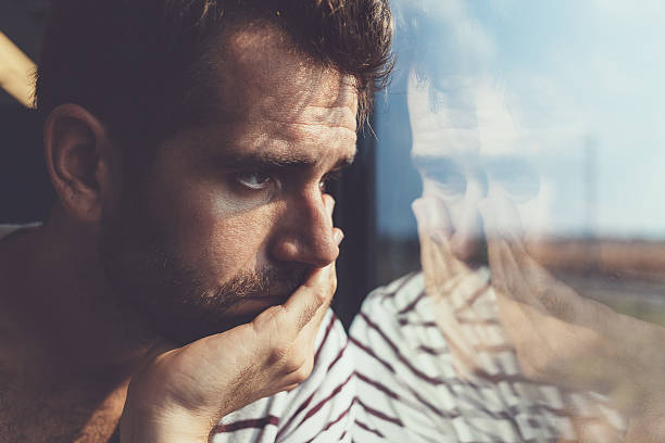 sad young man looking through the window - one man only stock pictures, royalty-free photos & images