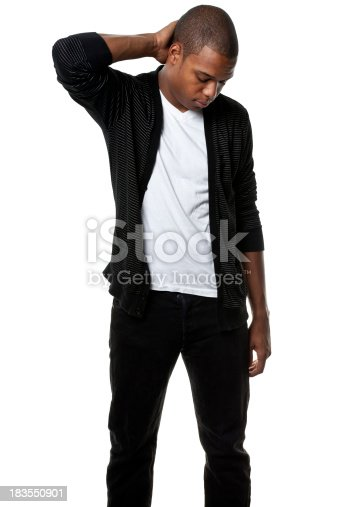 A young African American man scratches his head and looks downwards.