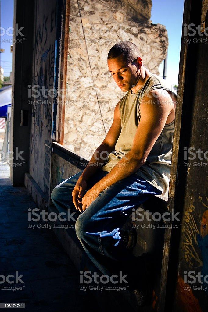 Sad Young Man Sitting on Wall royalty-free stock photo