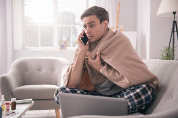triste jeune homme parle à son employeur - maladie photos et images de collection