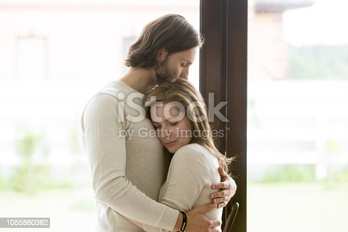 Sad young married couple embracing standing in living room opposite window at home. Sorrowful wife and husband feels unhappy, thinking about problems in relations, miscarriage, misbirth or infertility