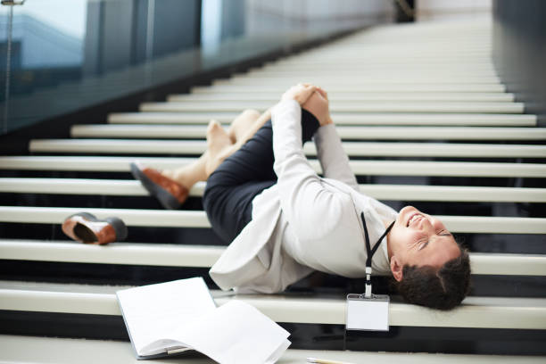 Sad young mixed race business lady feeling pain in knee lying on stair and holding knee, she falling down stairs stock photo