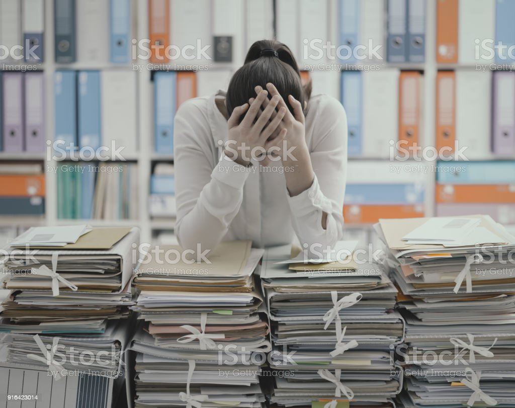Sad young office worker overloaded with work stock photo