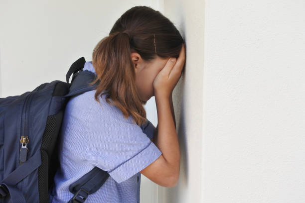 Sad young schoolgirl covering her face and crying against a wall stock photo