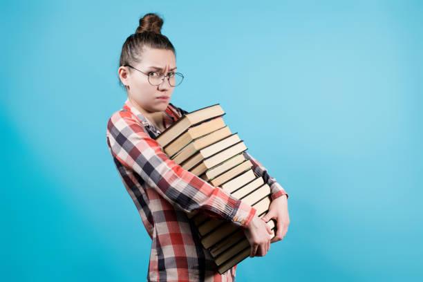 Triste joven estudiante en anteojos tiene un gran número de libros en sus manos - foto de stock