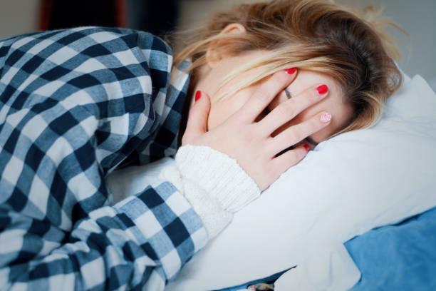 üzgün genç yorgun kadın yatakta yatıyordu - i̇nsan başı stok fotoğraflar ve resimler