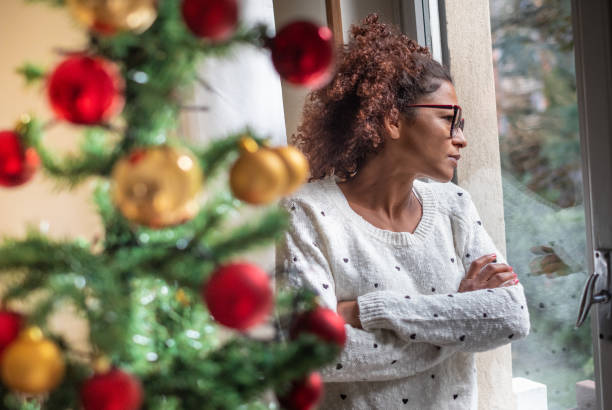 Sad young woman celebrating Christmas at home Pensive young black woman celebrating Christmas alone solitude stock pictures, royalty-free photos & images