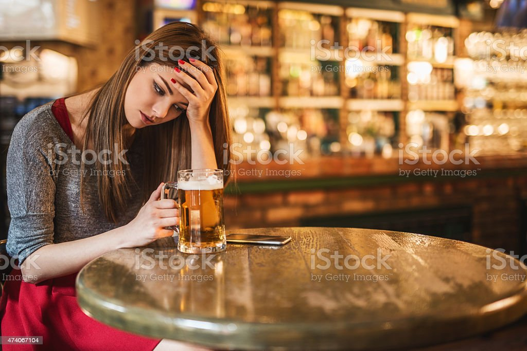 A young white woman in a gray sweater and red skirt resting her head on her hand and holding a large mug of beer in a bar.