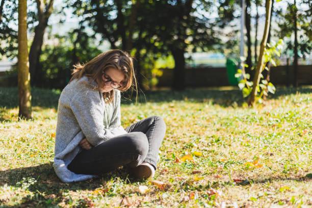 Sad young woman having period pain outdoors stock photo