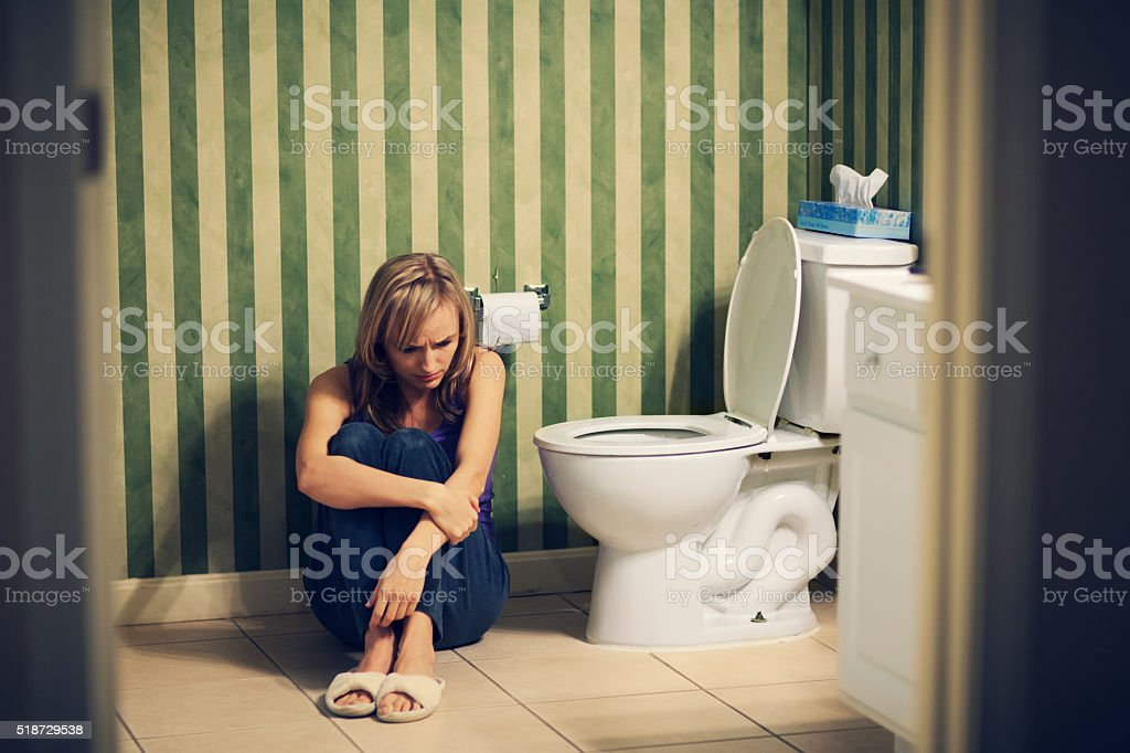 Sad young woman in bathroom stock photo