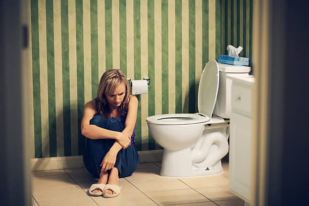 sad young woman in bathroom - constipation stock pictures, royalty-free photos & images
