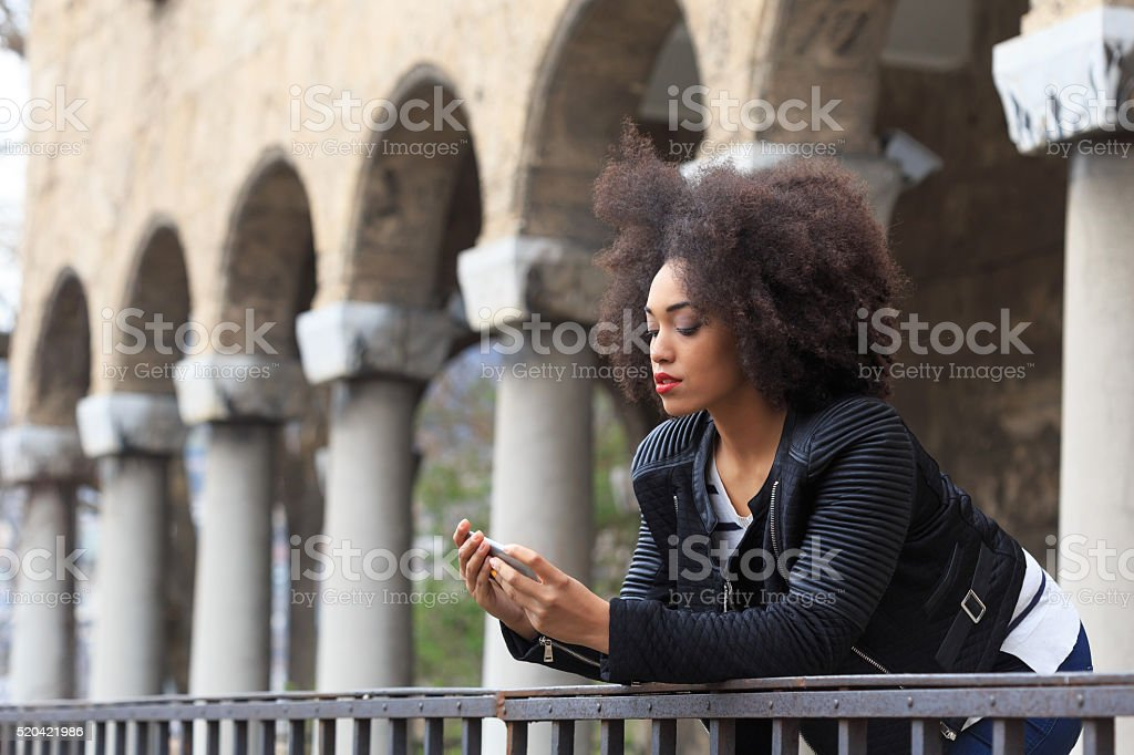 Sad young woman in front of ancient columns stock photo