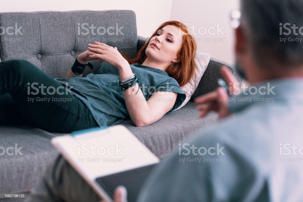 Traurige junge Frau auf einer graue Couch im Büro des Psychologen. Umgang mit Verlust-Konzept. Verschwommene Therapeuten im Vordergrund - Lizenzfrei Alkoholisches Getränk Stock-Foto