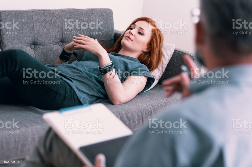 Sad young woman lying on a gray couch in psychologist's office. Coping with loss concept. Blurred therapist in the foreground – zdjęcie