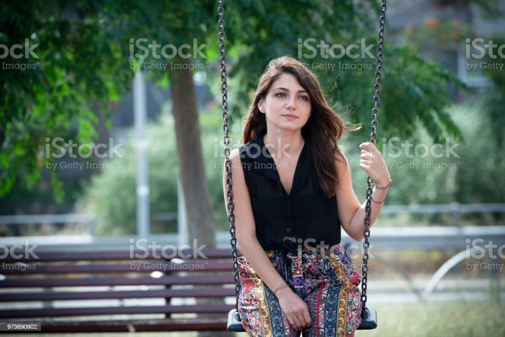 Sad young woman on the swing in the urban park - foto stock