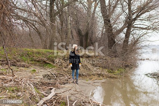 Sad young woman on the river shore in winter.