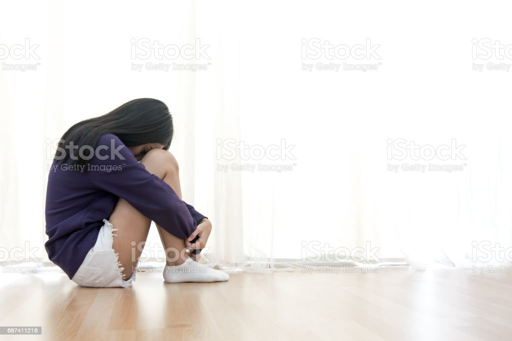 Sad young woman sit in her room and covering her face stock photo