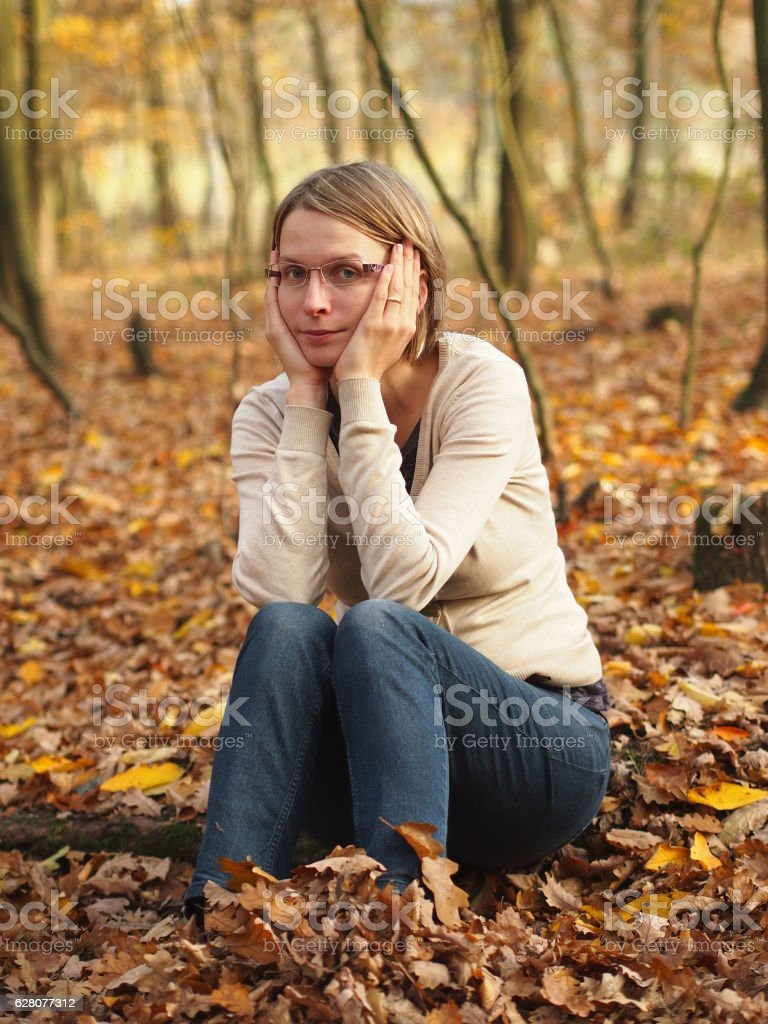 Sad young woman sitting in the autumn forest stock photo