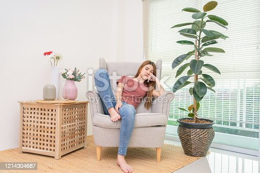 Sad young woman sitting on the sofa near window and flower vase at home, she is depressed and lonely, indoor