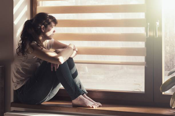Sad young woman sitting on the window at home isolated, watching out. Coronavirus quarantine concept. stock photo