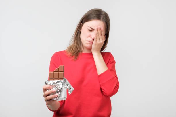 sad ung kvinna trött på diet begränsningar holding sweet chocolate - cravings bildbanksfoton och bilder