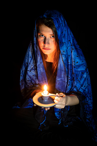 117149457 istock photo Sad young woman with candle and blue headscarf 1241211810