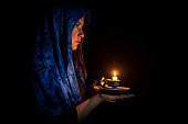 Sad young woman with candle and blue headscarf against black background