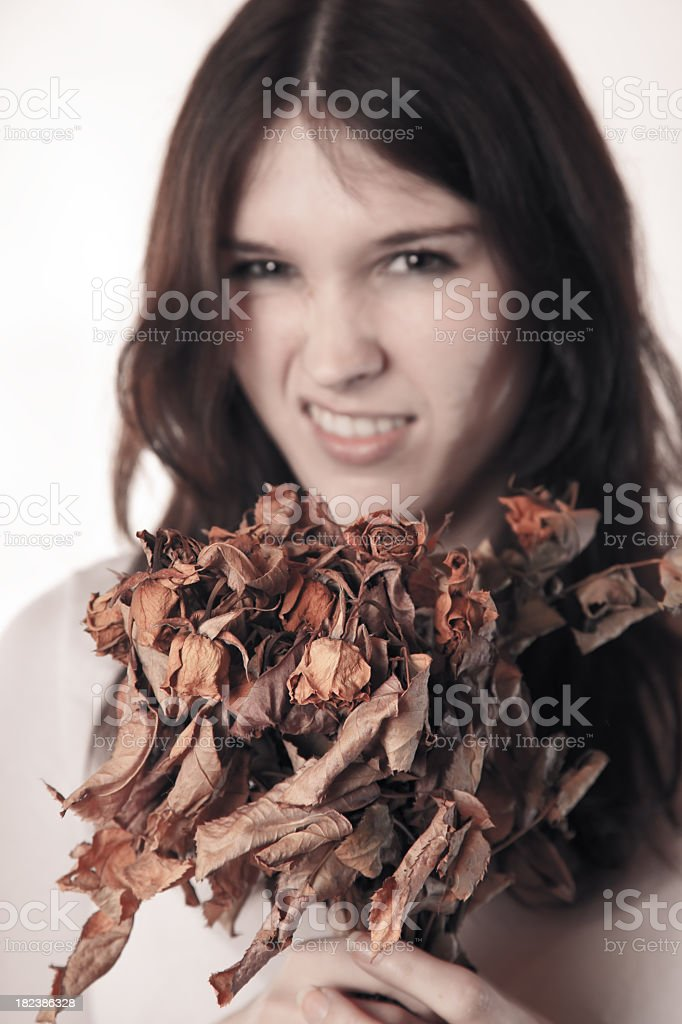 sad young woman with dry roses royalty-free stock photo