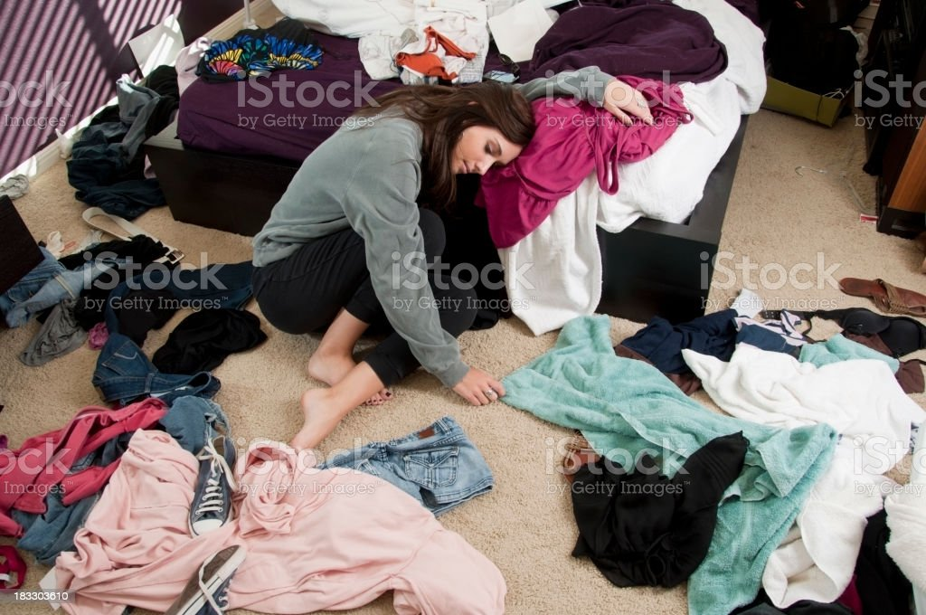 A young woman sadly contemplates the need to clean up her messy room....