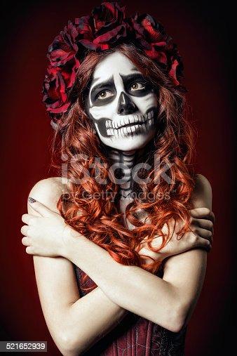 The sad young woman with muertos makeup (sugar skull)