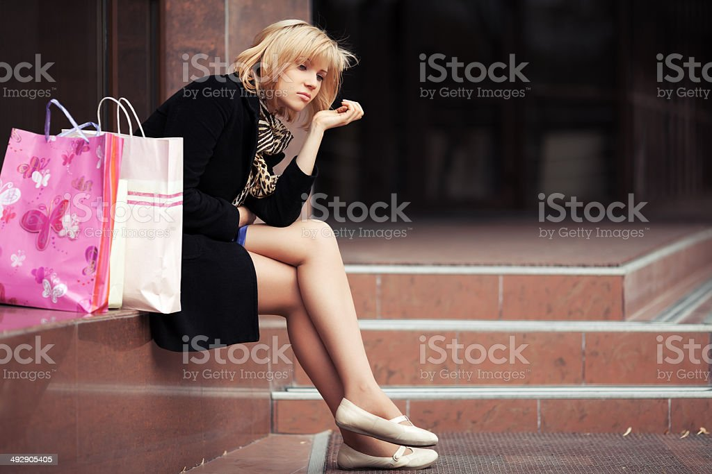 Sad young woman with shopping bags stock photo