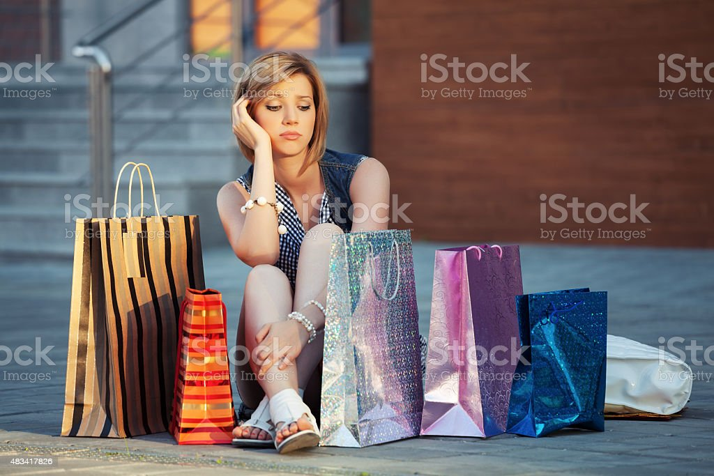 Sad young woman with shopping bags sitting on a sidewalk stock photo