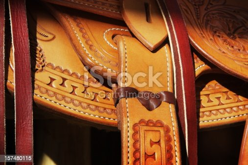 Saddle fender attachment in ornately worked Western leather cowboy tradition partially illuminated by sunset lighting.