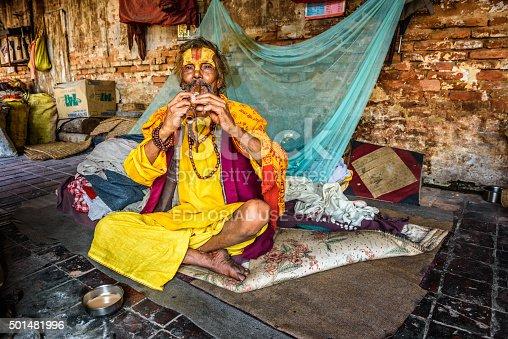 Kathmandu, Nepal - October 21, 2015 : Sadhu baba (holy man)  plays a pipe in the courtyard