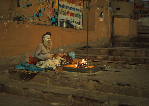 A Sadhu in winter night... on riverbanks of Ganges, at Varanasi A Sadhu, holy man, is sitting and making fire to warm himself in a cold winter night at Dashashwamedh Ghat of Varanasi, Uttar Pradesh.  Varanasi@ Uttar Pradesh is one the oldest living heritage cities of world and called spiritual capital of India. Though the city and its people have adopted new times, but still much of city has preserved the old charm. A unique mixture of old and modern times attracts travellers from all over the world. Photo taken at Varanasi, Uttar Pradesh on 11/17/2018 dashashwamedh ghat stock pictures, royalty-free photos & images