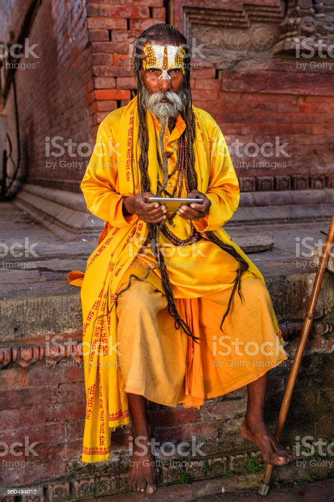 Sadhu - indian holyman using mobile phone stock photo
